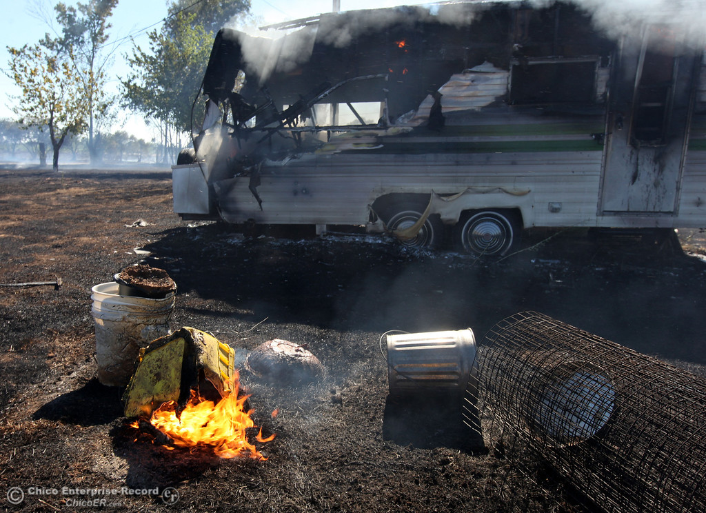 Description of . Items burn next to a smoldering trailer as Cal Fire - Butte County firefighters battle a fire off Vineyard Lane Friday, July 12, 2013 in Oroville, Calif.  (Jason Halley/Chico Enterprise-Record)