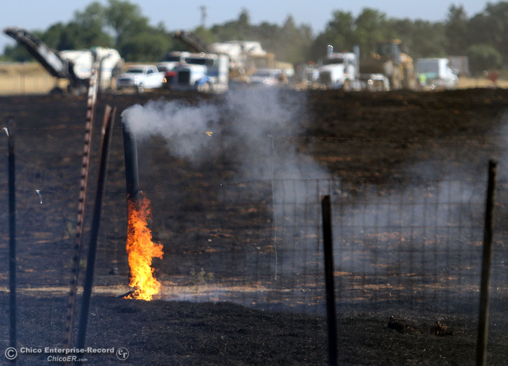 Description of . A fence post burns as Cal Fire - Butte County firefighters battle a fire off Vineyard Lane Friday, July 12, 2013 in Oroville, Calif.  (Jason Halley/Chico Enterprise-Record)