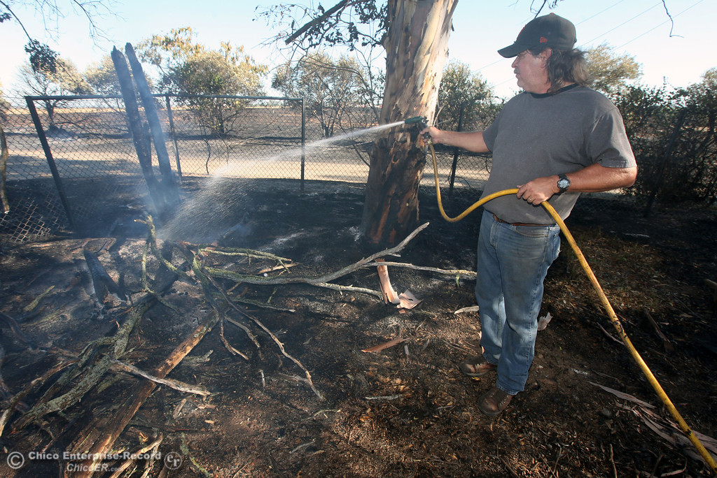 Description of . Scott Edberg hoses down vegetation that caught on fire as Cal Fire - Butte County firefighters battle a fire off Vineyard Lane Friday, July 12, 2013 in Oroville, Calif.  (Jason Halley/Chico Enterprise-Record)