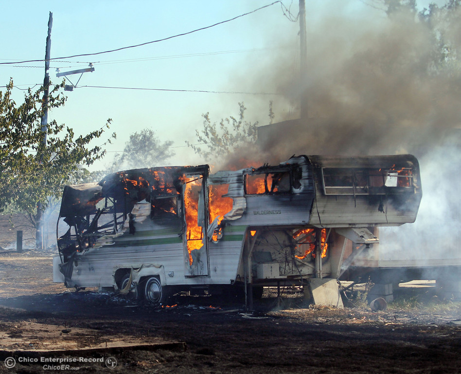 Description of . Flames shoot out of a trailer that caught on fire as Cal Fire - Butte County firefighters battle a fire off Vineyard Lane Friday, July 12, 2013 in Oroville, Calif.  (Jason Halley/Chico Enterprise-Record)