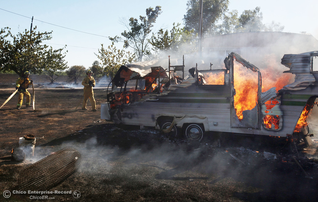 Description of . Cal Fire - Butte County firefighters Brad Padilla (left) and Ibe Liebenberg (center) battle a fire burning a trailer off Vineyard Lane Friday, July 12, 2013 in Oroville, Calif.  (Jason Halley/Chico Enterprise-Record)