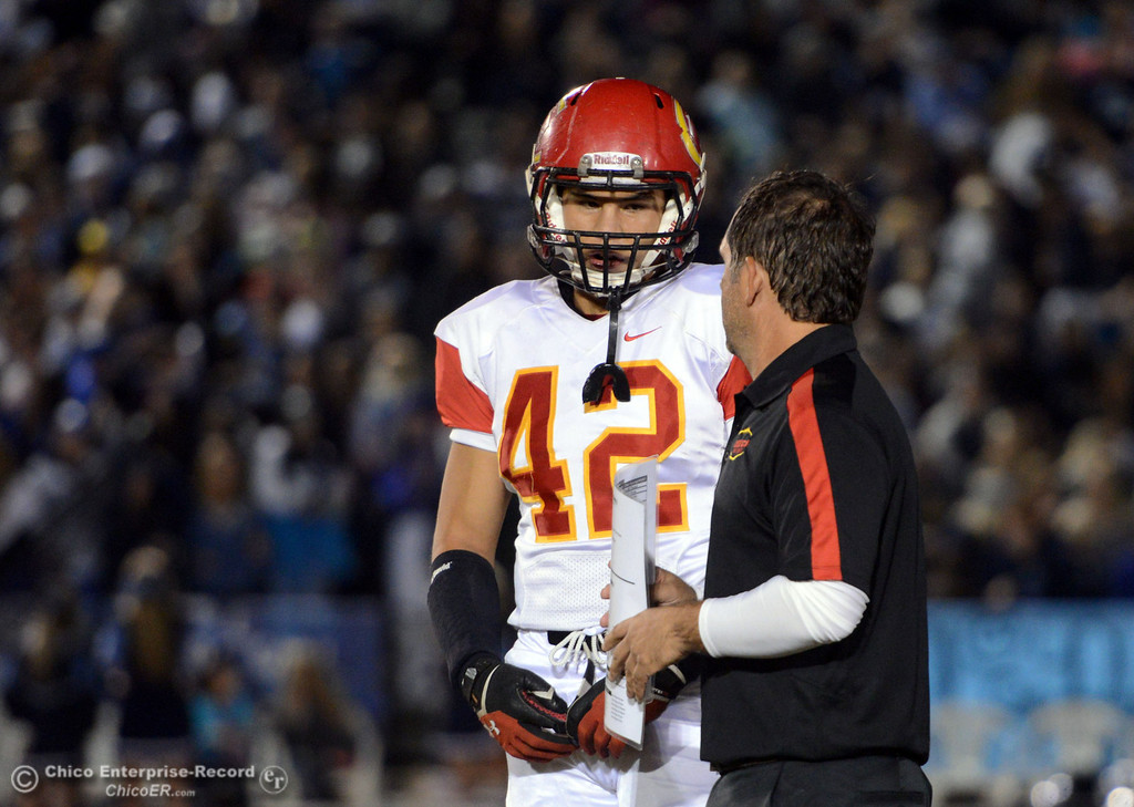 Description of . Chico High\'s #42 Nate Guanzon (left) talks with coach Jason Alvistur (right) against Pleasant Valley High in the first quarter of their Almond Bowl football game at CSUC University Stadium Friday, November 1, 2013 in Chico, Calif.  (Jason Halley/Chico Enterprise-Record)