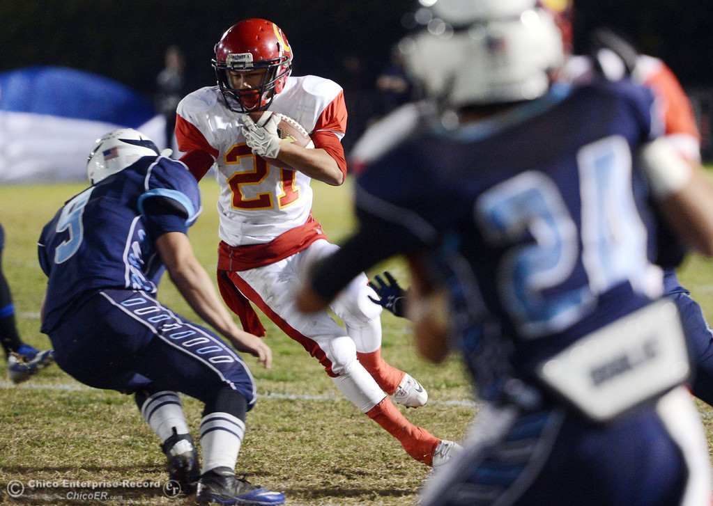 Description of . Chico High\'s #21 Cameron Alfaro (right) rushes against Pleasant Valley High\'s #9 Houston McGowan (left) in the first quarter of their Almond Bowl football game at CSUC University Stadium Friday, November 1, 2013 in Chico, Calif.  (Jason Halley/Chico Enterprise-Record)