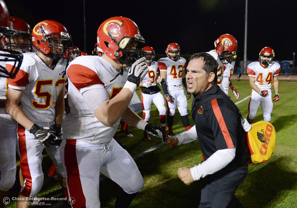 Description of . Chico High\'s coach Jason Alvistur (right) riles up the team against Pleasant Valley High in the first quarter of their Almond Bowl football game at CSUC University Stadium Friday, November 1, 2013 in Chico, Calif.  (Jason Halley/Chico Enterprise-Record)