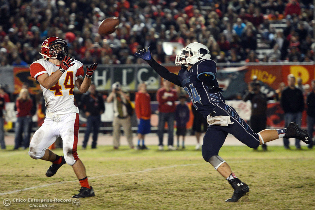 Description of . Chico High\'s #44 Paolo DiSano (left) catches against Pleasant Valley High\'s #34 Cale Crawford (right) in the second quarter of their Almond Bowl football game at CSUC University Stadium Friday, November 1, 2013 in Chico, Calif.  (Jason Halley/Chico Enterprise-Record)