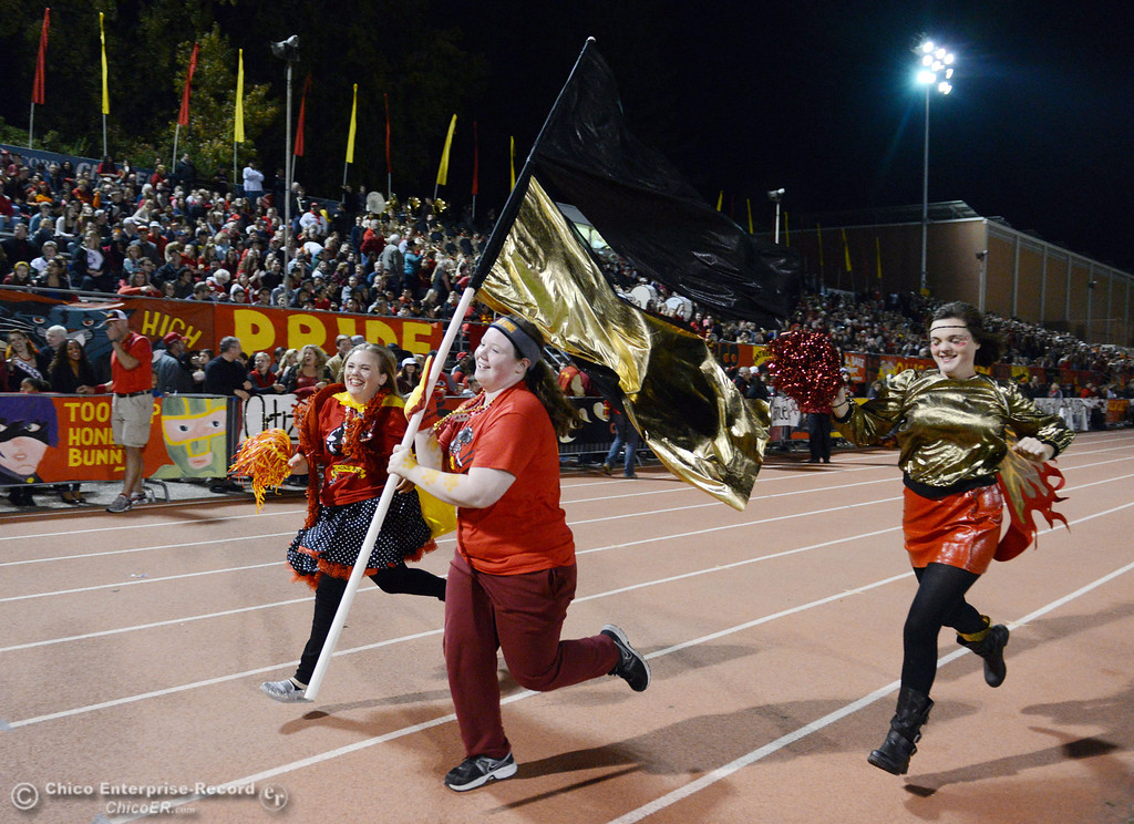 Description of . Chico High fans run down the track to cheer on against Pleasant Valley High in the first quarter of their Almond Bowl football game at CSUC University Stadium Friday, November 1, 2013 in Chico, Calif.  (Jason Halley/Chico Enterprise-Record)