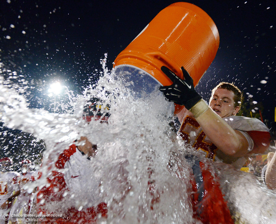 Description of . Chico High\'s #58 Malik Hopkins (right) pours a bucket of water of coaches Kevin Wisdom (left) and Jason Alvistur (center) against Pleasant Valley High in the fourth quarter of their Almond Bowl football game at CSUC University Stadium Friday, November 1, 2013 in Chico, Calif.  (Jason Halley/Chico Enterprise-Record)
