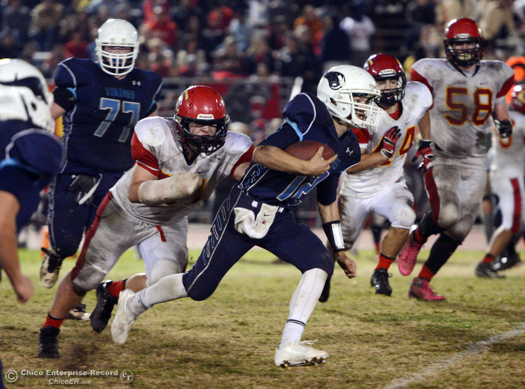 Description of . Pleasant Valley High\'s #12 Trent Darms (right) runs against Chico High\'s #51 Kody Sonday (left) in the third quarter of their Almond Bowl football game at CSUC University Stadium Friday, November 1, 2013 in Chico, Calif.  (Jason Halley/Chico Enterprise-Record)