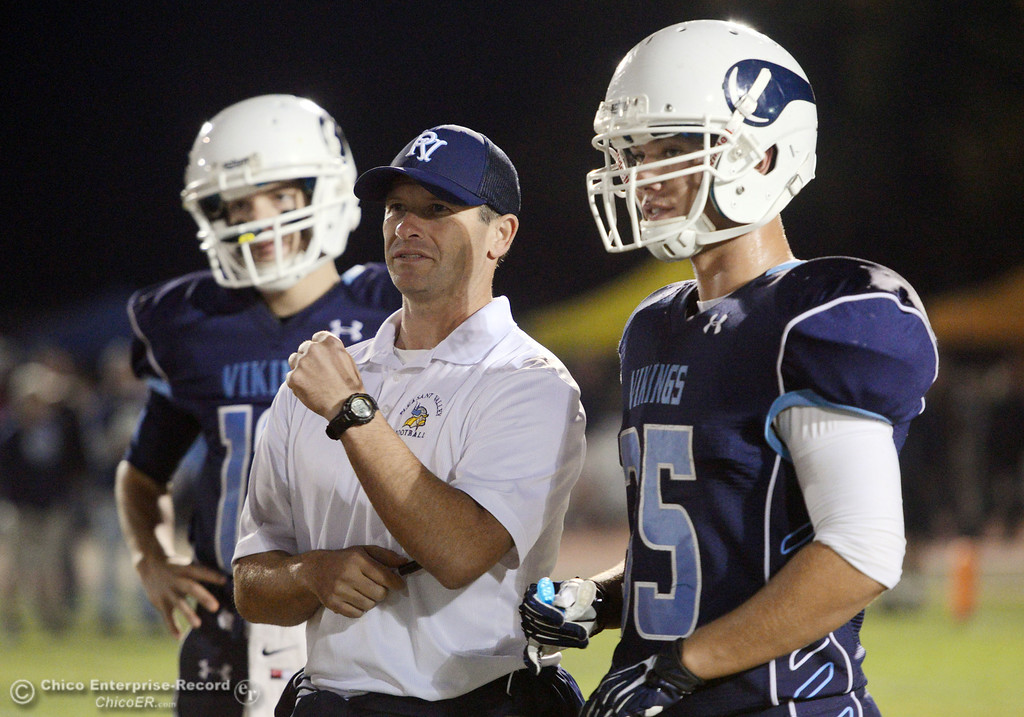 Description of . Pleasant Valley High\'s coach Mark Cooley (center) and #35 Benjamin Whitmore (right) against Chico High in the first quarter of their Almond Bowl football game at CSUC University Stadium Friday, November 1, 2013 in Chico, Calif.  (Jason Halley/Chico Enterprise-Record)