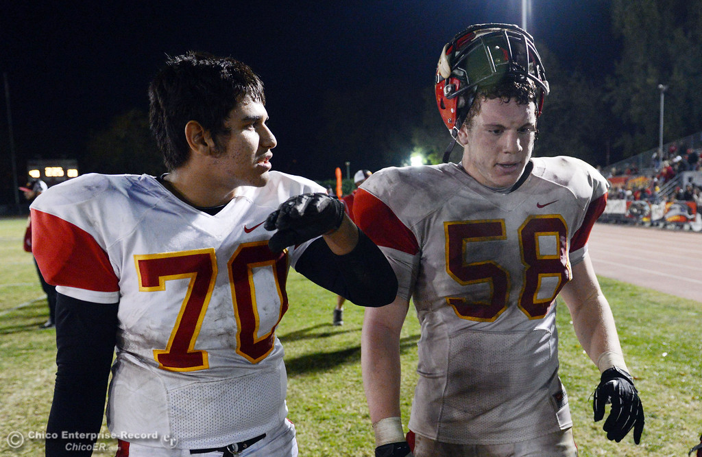 Description of . Chico High\'s #70 Juan Ortiz (left) and #58 Malik Hopkins (right) against Pleasant Valley High in the fourth quarter of their Almond Bowl football game at CSUC University Stadium Friday, November 1, 2013 in Chico, Calif.  (Jason Halley/Chico Enterprise-Record)