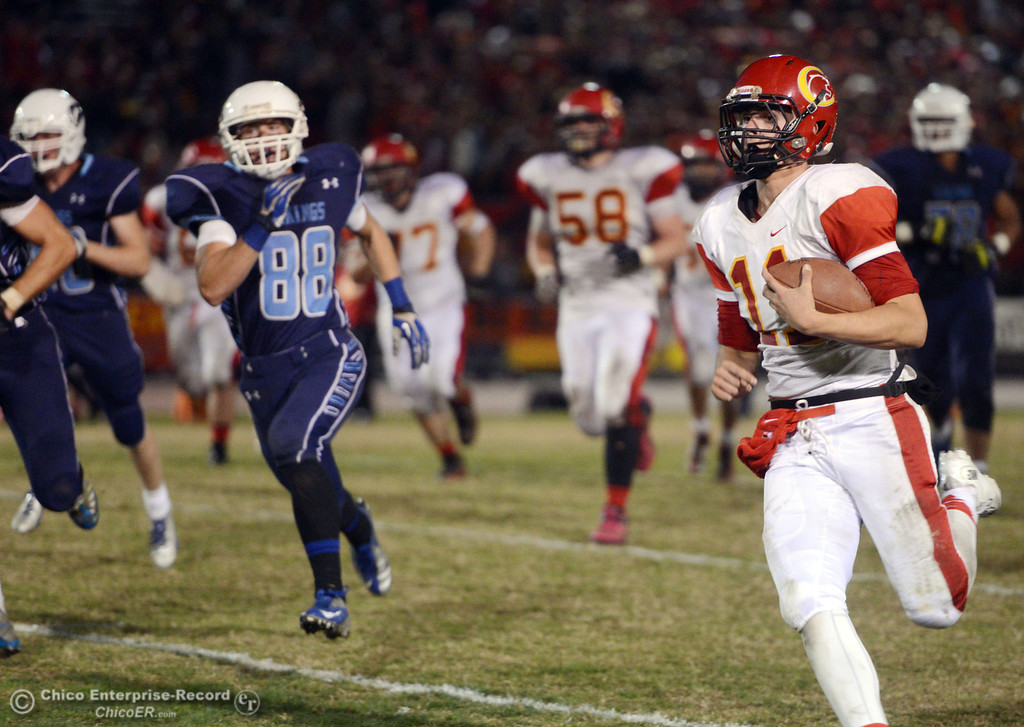 Description of . Chico High\'s #11 Clayton Welch runs the ball for a first down against Pleasant Valley High\'s #88 Zack Suttles (left) in the second quarter of their Almond Bowl football game at CSUC University Stadium Friday, November 1, 2013 in Chico, Calif.  (Jason Halley/Chico Enterprise-Record)