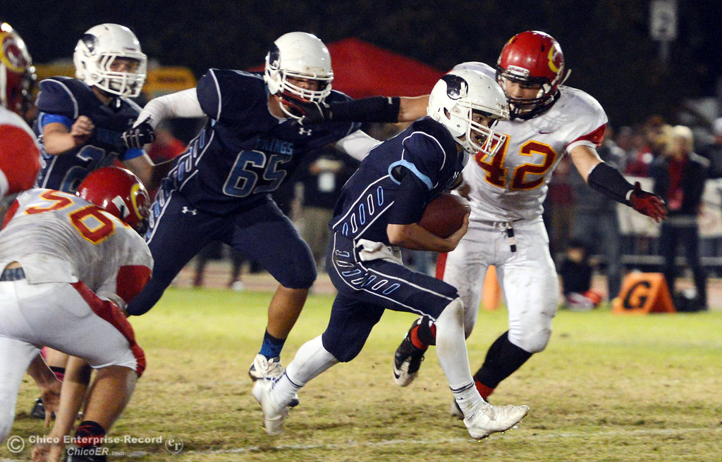 Description of . Chico High\'s #42 Nate Guanzon (right) tackels against Pleasant Valley High\'s #12 Trent Darms (left) in the second quarter of their Almond Bowl football game at CSUC University Stadium Friday, November 1, 2013 in Chico, Calif.  (Jason Halley/Chico Enterprise-Record)