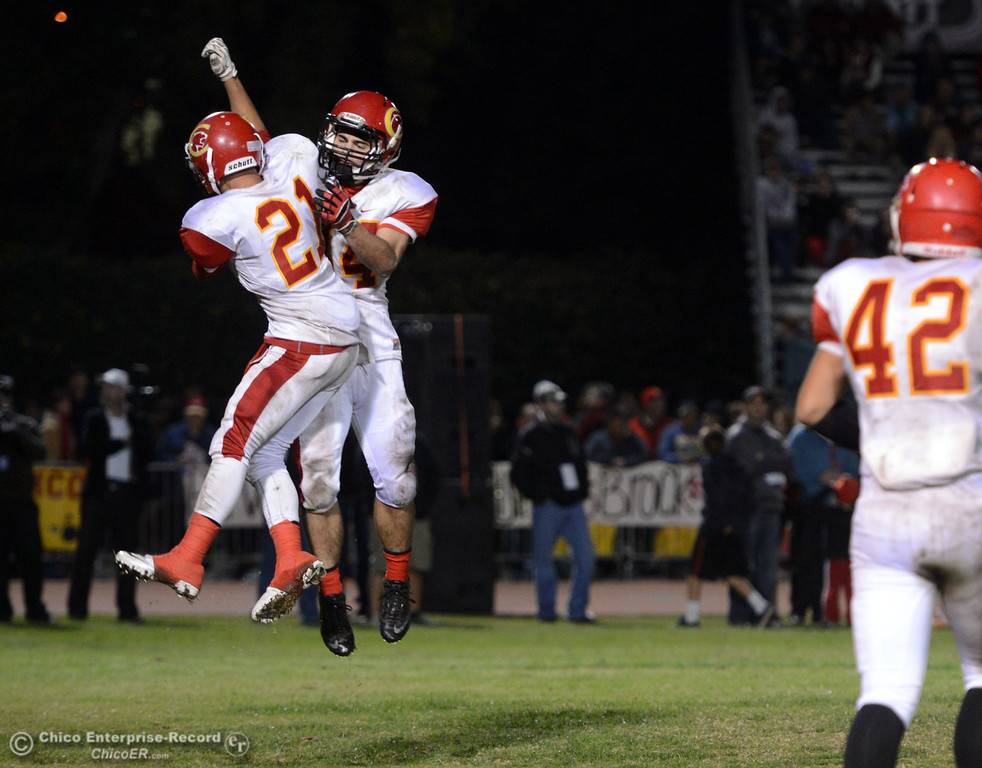 Description of . Chico High\'s #21 Cameron Alfaro (left) celebrates on scoring a touchdown with #44 Paolo DiSano (right) against Pleasant Valley High in the third quarter of their Almond Bowl football game at CSUC University Stadium Friday, November 1, 2013 in Chico, Calif.  (Jason Halley/Chico Enterprise-Record)