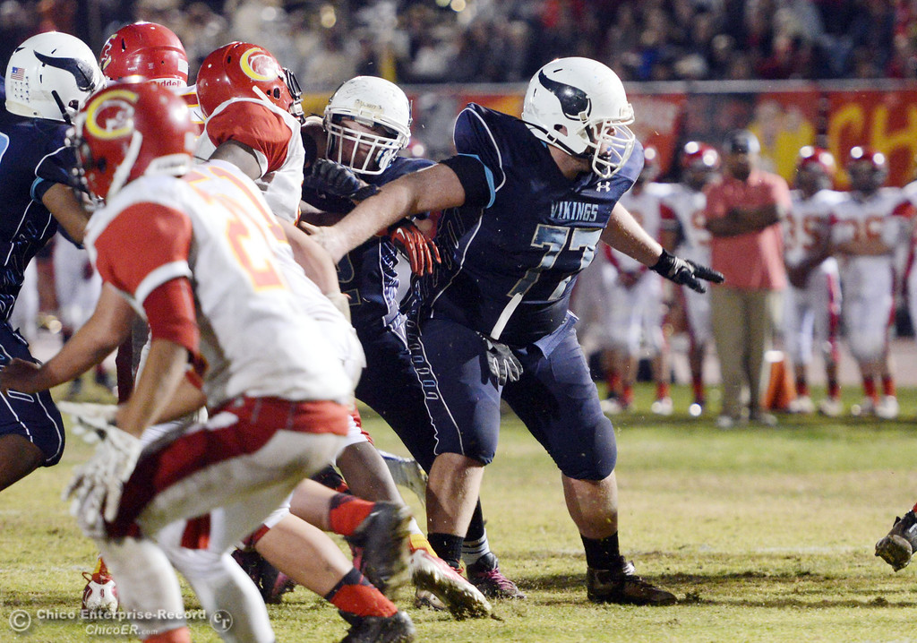 Description of . Pleasant Valley High\'s #77 Tyler Stimac (center) blocks against Chico High in the third quarter of their Almond Bowl football game at CSUC University Stadium Friday, November 1, 2013 in Chico, Calif.  (Jason Halley/Chico Enterprise-Record)