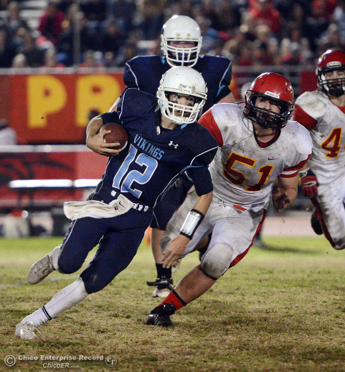 Description of . Pleasant Valley High\'s #12 Trent Darms (left) runs against Chico High\'s #51 Kody Sonday (right) in the third quarter of their Almond Bowl football game at CSUC University Stadium Friday, November 1, 2013 in Chico, Calif.  (Jason Halley/Chico Enterprise-Record)