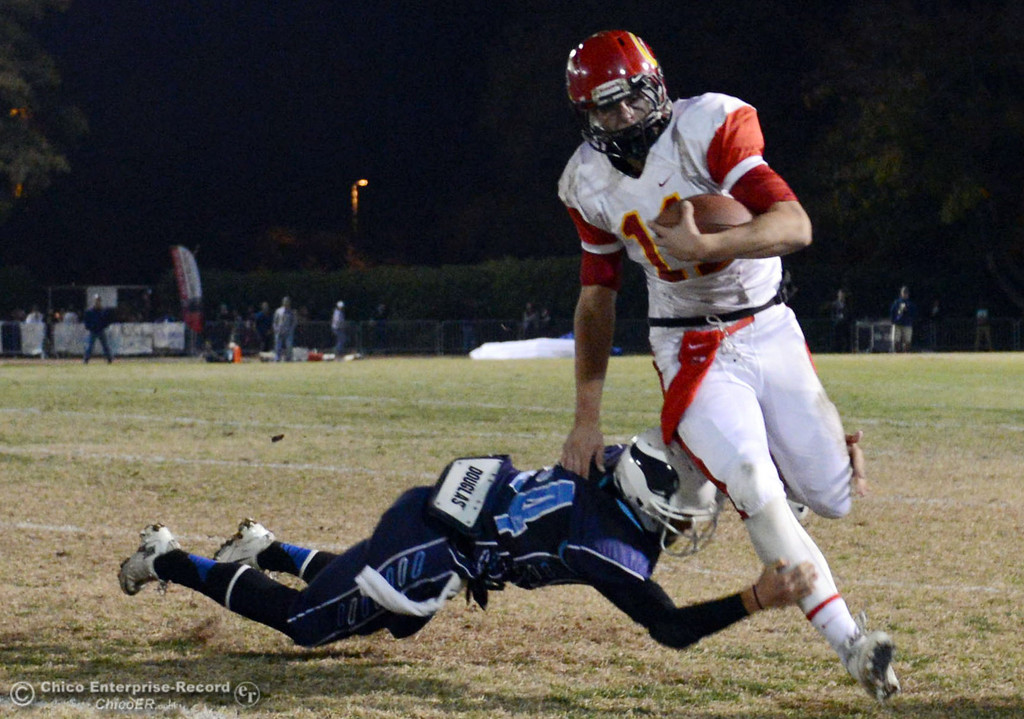 Description of . Chico High\'s #11 Clayton Welch (right) is tackled against Pleasant Valley High\'s #24 Jack Soza (left) in the first quarter of their Almond Bowl football game at CSUC University Stadium Friday, November 1, 2013 in Chico, Calif.  (Jason Halley/Chico Enterprise-Record)