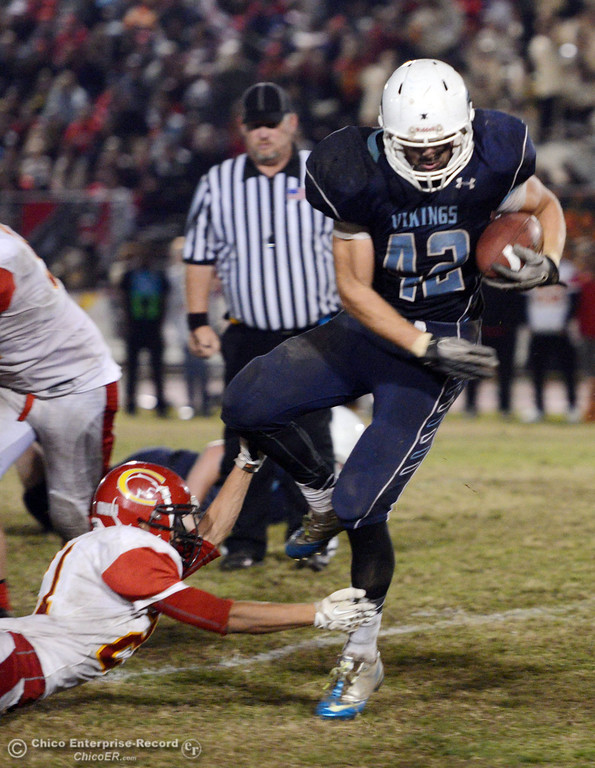 Description of . Chico High\'s #21 Cameron Alfaro (left) tackles Pleasant Valley High\'s #42 Chad Olsen (right) in the third quarter of their Almond Bowl football game at CSUC University Stadium Friday, November 1, 2013 in Chico, Calif.  (Jason Halley/Chico Enterprise-Record)