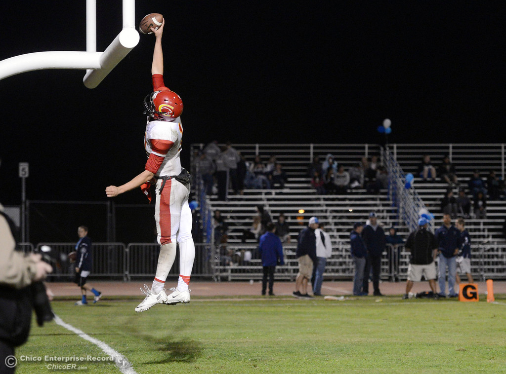 Description of . Chico High\'s #11 Clayton Welch dunks the football over the goal posts after scoring a touchdown against Pleasant Valley High in the fourth quarter of their Almond Bowl football game at CSUC University Stadium Friday, November 1, 2013 in Chico, Calif.  (Jason Halley/Chico Enterprise-Record)