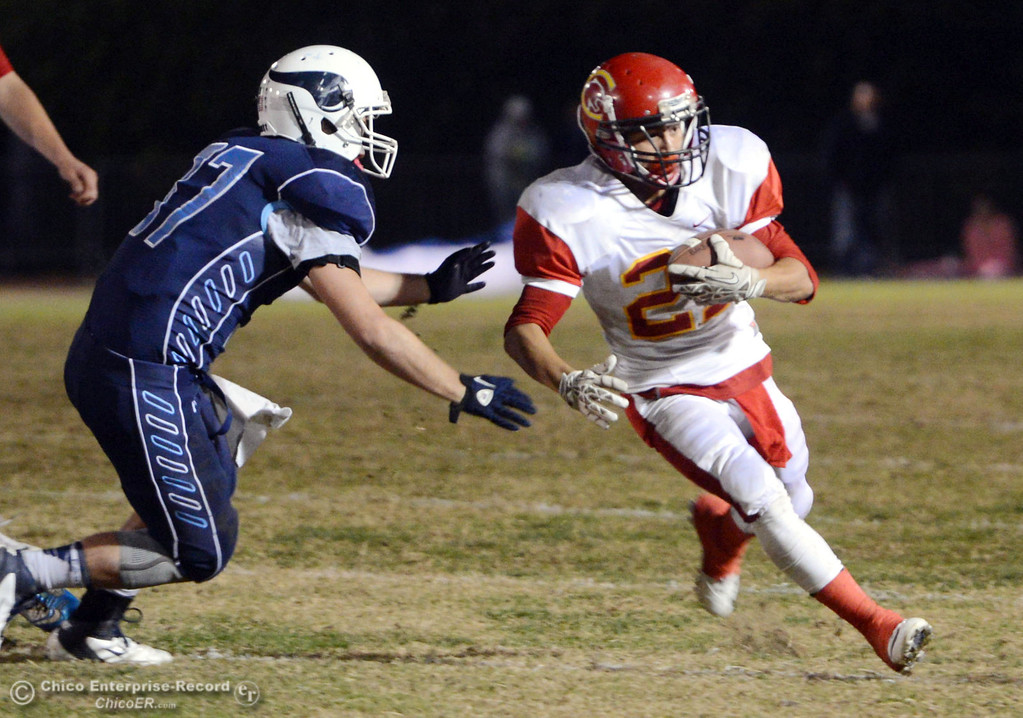 Description of . Chico High\'s #21 Cameron Alfaro (right) rushes against Pleasant Valley High\'s #37 Garett Greenwald (left) in the first quarter of their Almond Bowl football game at CSUC University Stadium Friday, November 1, 2013 in Chico, Calif.  (Jason Halley/Chico Enterprise-Record)