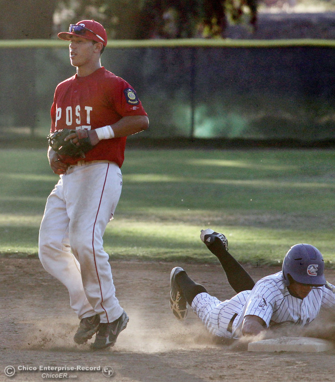 Description of . Chico Nuts' #7 Ryan Souza (right) slides safely back to second base in a pickoff attempt against Yolo Post 77's #5 Michael Chavarria (left) in the bottom of the first inning during their American Legion baseball game at Doryland Field Thursday, July 18, 2013 in Chico, Calif.  (Jason Halley/Chico Enterprise-Record)