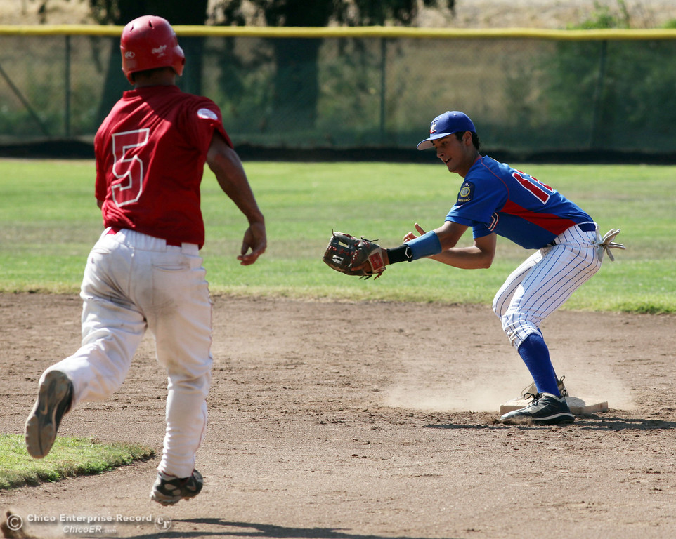 . Chico Nuts\' #12 Michael Sanderson (right) turns the double play from second base against Yolo Post 77\'s #5 Michael Chavarria (left) in the top of the third inning during their American Legion baseball game at Doryland field Saturday, July 20, 2013 in Chico, Calif.  (Jason Halley/Chico Enterprise-Record)