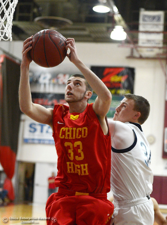 Description of . Chico High's #33 Devein Bauer (left) takes a shot against Pleasant Valley High's #34 Brandt Hughes (right) in the first quarter of their boys basketball game at Acker Gym Saturday, March 8, 2014 in Chico, Calif.  (Jason Halley - Enterprise-Record)