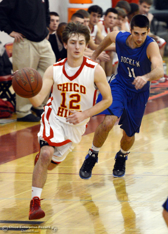 Description of . Chico High's #12 Sterling Winter (left) dribbles against Rocklin High's #11 Tyler Chimirusti (right) in the second quarter of their boys basketball game at CHS Tuesday, January 7, 2014 in Chico, Calif.  (Jason Halley/Chico Enterprise-Record)
