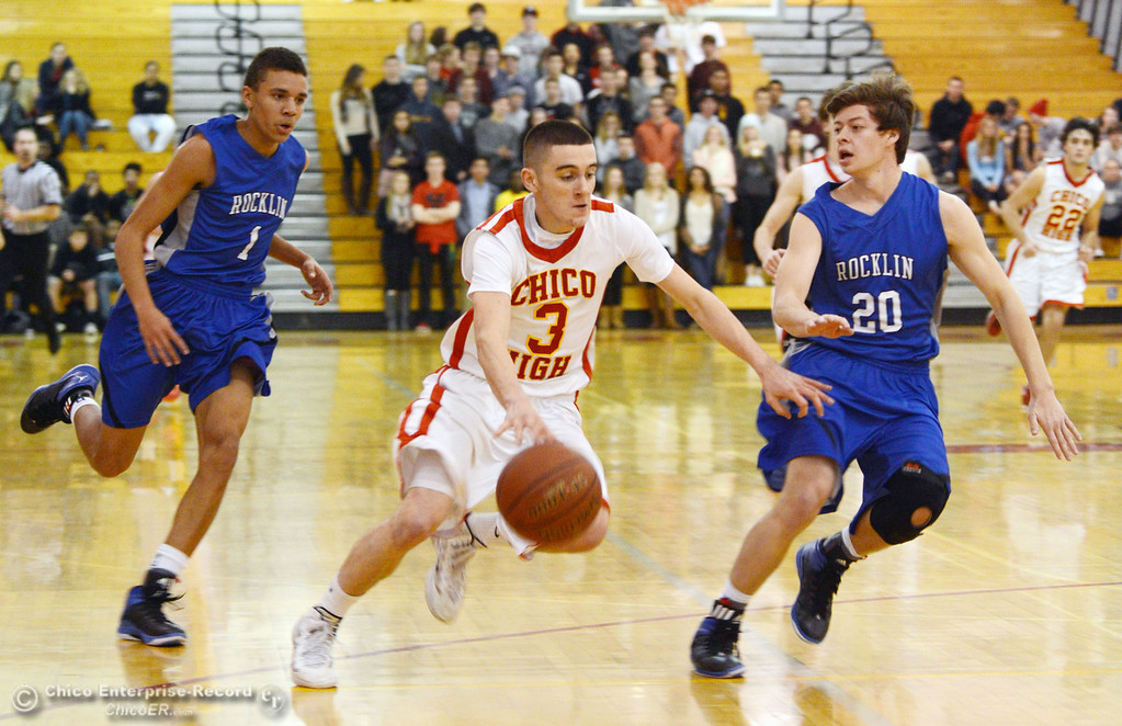 Description of . Chico High's #3 Myles Lawing (center) dribbles against Rocklin High's #1 Seth Bradley (left) and #20 Jake Toto (right) in the second quarter of their boys basketball game at CHS Tuesday, January 7, 2014 in Chico, Calif.  (Jason Halley/Chico Enterprise-Record)