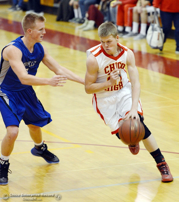 Description of . Chico High's #21 Hunter Mootz (right) dribbles against Rocklin High's #3 Cole Bridge (left) in the second quarter of their boys basketball game at CHS Tuesday, January 7, 2014 in Chico, Calif.  (Jason Halley/Chico Enterprise-Record)