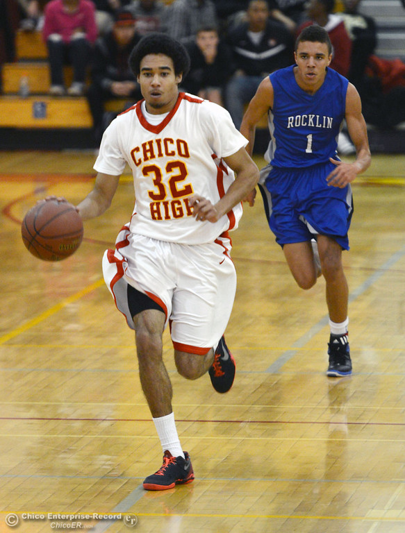 Description of . Chico High's #32 Uvonte Person (left) dribbles against Rocklin High's #1 Seth Bradley (right) in the second quarter of their boys basketball game at CHS Tuesday, January 7, 2014 in Chico, Calif.  (Jason Halley/Chico Enterprise-Record)