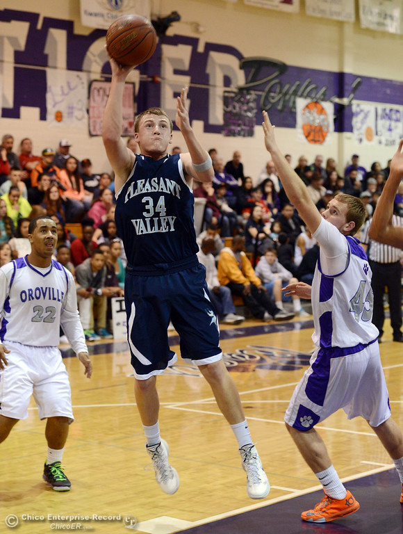 . Pleasant Valley High\'s #34 Brandt Hughes (left) goes up for a shot against Oroville High\'s #22 James Jones (left) and #45 Eric Laster (right) in the first quarter of their boys basketball game at OHS Wednesday, February 19, 2014 in Oroville, Calif.  (Jason Halley/Chico Enterprise-Record)