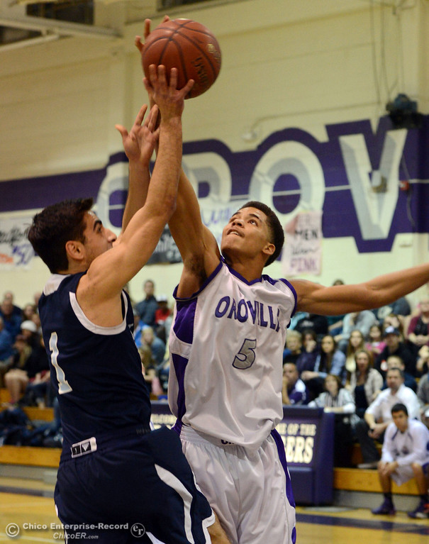 . Pleasant Valley High\'s #1 Joseph Abdulmasih (left) shot is blocked against Oroville High\'s #5 Kahliel Wyatt (right) in the first quarter of their boys basketball game at OHS Wednesday, February 19, 2014 in Oroville, Calif.  (Jason Halley/Chico Enterprise-Record)