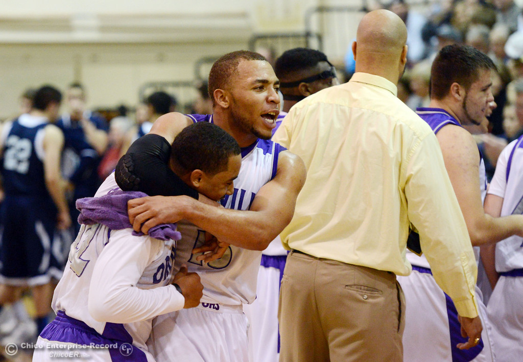 . Oroville High\'s #22 James Jones (left) is embraced by #15 Derrek Gordon (right) after making a shot at the end of the first quarter of their boys basketball game at OHS Wednesday, February 19, 2014 in Oroville, Calif.  (Jason Halley/Chico Enterprise-Record)