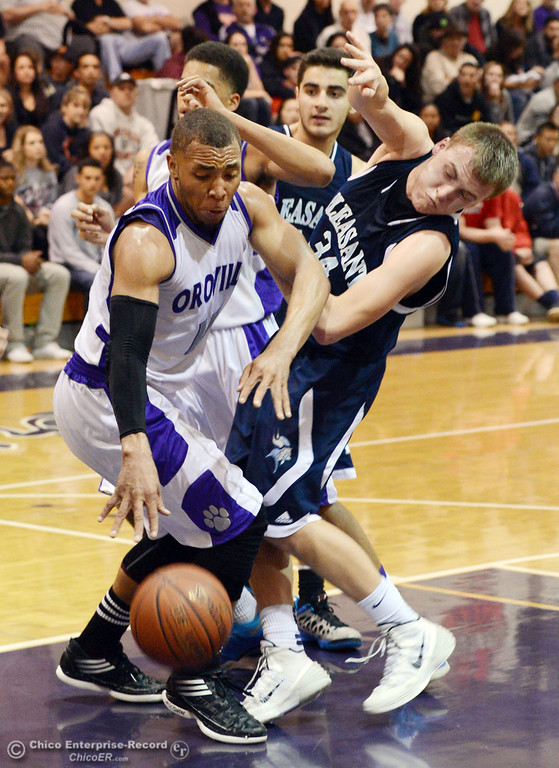 . Oroville High\'s #15 Derrek Gordon (left) dribbles against Pleasant Valley High\'s #34 Brandt Hughes (right) in the fourth quarter of their boys basketball game at OHS Wednesday, February 19, 2014 in Oroville, Calif.  (Jason Halley/Chico Enterprise-Record)