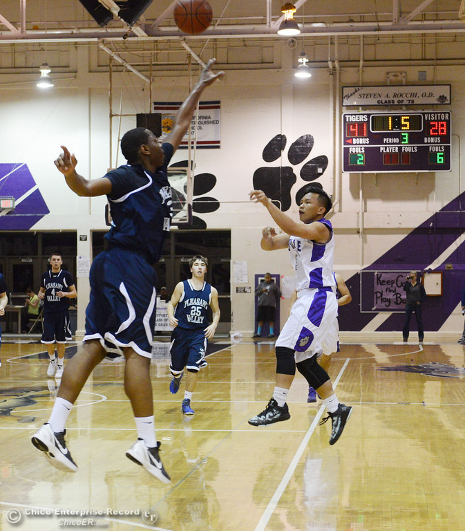 . Oroville High\'s #3 William Xiong (right) takes a shot against Pleasant Valley High\'s #32 Javonne McClellan (left) in the third quarter of their boys basketball game at OHS Wednesday, February 19, 2014 in Oroville, Calif.  (Jason Halley/Chico Enterprise-Record)