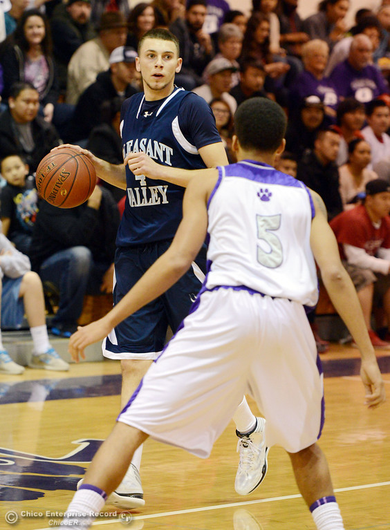 . Pleasant Valley High\'s #4 Jerry Migasi (left) dribbles against Oroville High\'s #5 Kahliel Wyatt (right) in the first quarter of their boys basketball game at OHS Wednesday, February 19, 2014 in Oroville, Calif.  (Jason Halley/Chico Enterprise-Record)