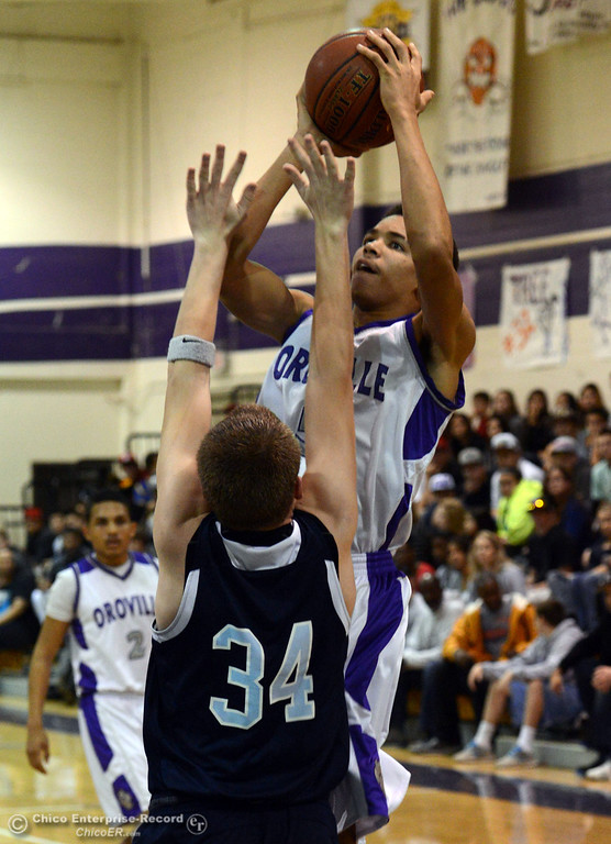 . Oroville High\'s #15 Derrek Gordon (top) against Pleasant Valley High\'s #34 Brandt Hughes (front) in the second quarter of their boys basketball game at OHS Wednesday, February 19, 2014 in Oroville, Calif.  (Jason Halley/Chico Enterprise-Record)