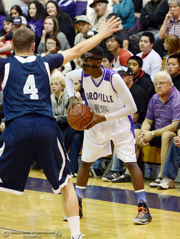 . Oroville High\'s #12 Jabari Jenkins (right) looks to pass against Pleasant Valley High\'s #4 Jerry Migasi (left) in the second quarter of their boys basketball game at OHS Wednesday, February 19, 2014 in Oroville, Calif.  (Jason Halley/Chico Enterprise-Record)