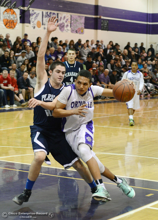 . Oroville High\'s #2 Marcus Wilhite (right) dribbles against Pleasant Valley High\'s #22 Tyler Schnerringer (left) in the fourth quarter of their boys basketball game at OHS Wednesday, February 19, 2014 in Oroville, Calif.  (Jason Halley/Chico Enterprise-Record)