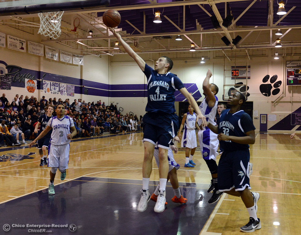 . Pleasant Valley High\'s #4 Jerry Migasi (center) goes up for a shot against Oroville High in the first quarter of their boys basketball game at OHS Wednesday, February 19, 2014 in Oroville, Calif.  (Jason Halley/Chico Enterprise-Record)