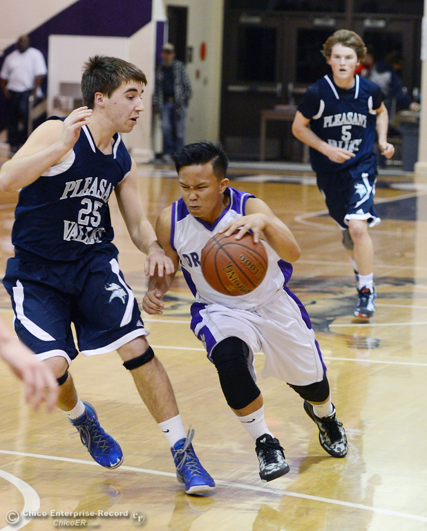 . Oroville High\'s #3 William Xiong (right) dribbles against Pleasant Valley High\'s #25 Wes Kokal (left) in the fourth quarter of their boys basketball game at OHS Wednesday, February 19, 2014 in Oroville, Calif.  (Jason Halley/Chico Enterprise-Record)