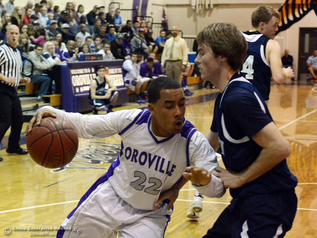 . Oroville High\'s #22 James Jones (left) dribbles against Pleasant Valley High\'s #5 Tyler Collier (right) in the second quarter of their boys basketball game at OHS Wednesday, February 19, 2014 in Oroville, Calif.  (Jason Halley/Chico Enterprise-Record)