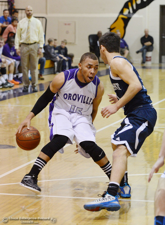 . Oroville High\'s #15 Derrek Gordon (left) dribbles against Pleasant Valley High\'s #1 Joseph Abdulmasih (right) in the second quarter of their boys basketball game at OHS Wednesday, February 19, 2014 in Oroville, Calif.  (Jason Halley/Chico Enterprise-Record)
