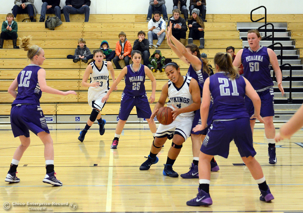 Description of . Pleasant Valley High's #4 Dominique Jackson (center) drives to the basket against Petaluma High in the first quarter of their girls basketball game at PVHS Varley Gym Friday, December 6, 2013 in Chico, Calif. (Jason Halley/Chico Enterprise-Record)