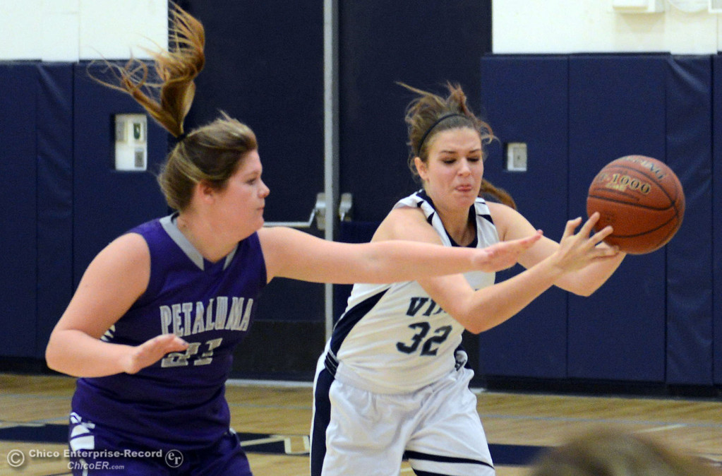 Description of . Pleasant Valley High's #32 Natalie Makel (right) dribbles against Petaluma High's #21 Cassie Baddeley (left0 in the first quarter of their girls basketball game at PVHS Varley Gym Friday, December 6, 2013 in Chico, Calif. (Jason Halley/Chico Enterprise-Record)