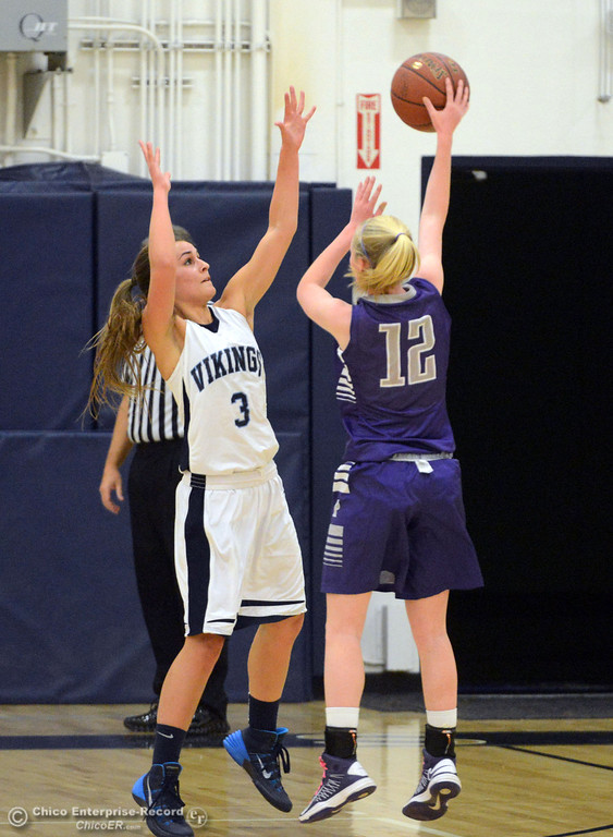 Description of . Pleasant Valley High's #3 Izzy Bonacorsi (left) goes up to block against Petaluma High's #12 Jenna Teagarden (right) in the first quarter of their girls basketball game at PVHS Varley Gym Friday, December 6, 2013 in Chico, Calif. (Jason Halley/Chico Enterprise-Record)