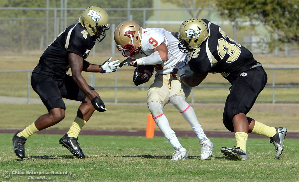 Description of . Butte College's #4 Chris Edwards (left) and #32 Brian Anderson (right) takcle against De Anza College's #9 Justin Arcune (center) in the second quarter of their football game at Butte's Cowan Stadium Saturday, October 26, 2013 in Oroville, Calif.  (Jason Halley/Chico Enterprise-Record)