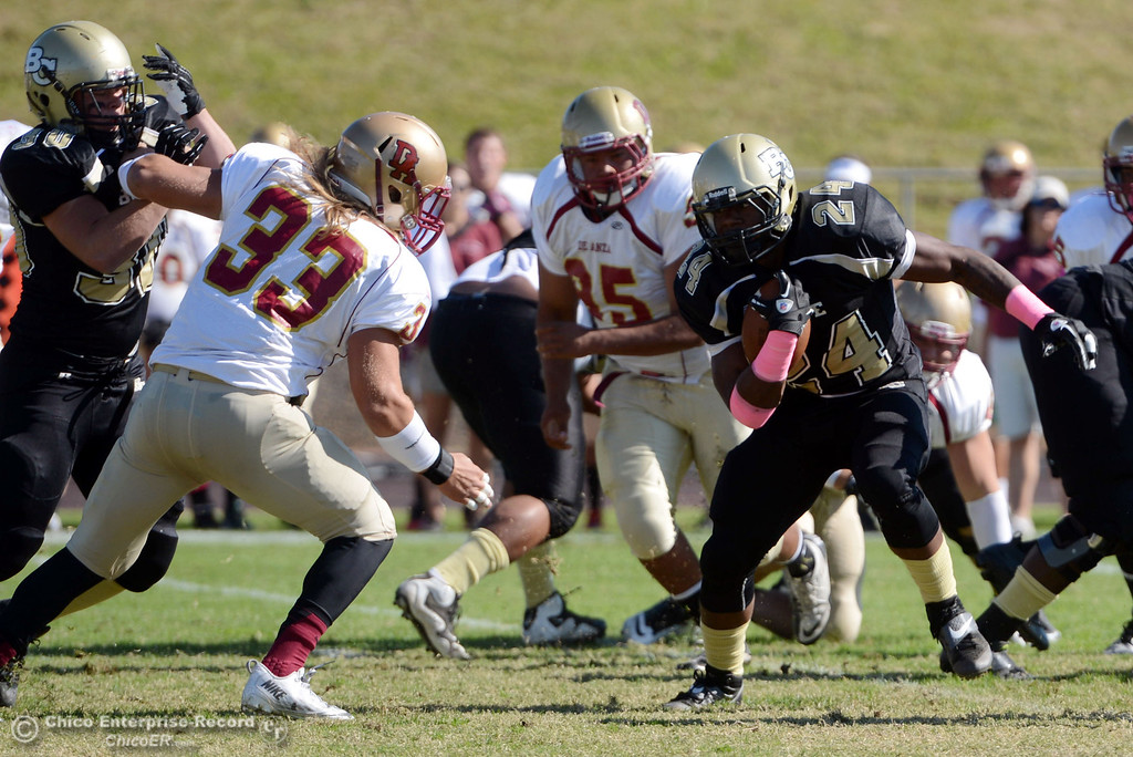 Description of . Butte College\'s #24 Kendall Williams (right) rushes against De Anza College\'s #33 Chuck Sullivan (left) in the first quarter of their football game at Butte\'s Cowan Stadium Saturday, October 26, 2013 in Oroville, Calif.  (Jason Halley/Chico Enterprise-Record)