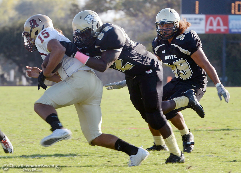 Description of . Butte College's #99 Leopeni Siania (right) watches #52 Kyjuan Tate (center) tackles against De Anza College's #15 Paris Shaw (left) in the fourth quarter of their football game at Butte's Cowan Stadium Saturday, October 26, 2013 in Oroville, Calif.  (Jason Halley/Chico Enterprise-Record)