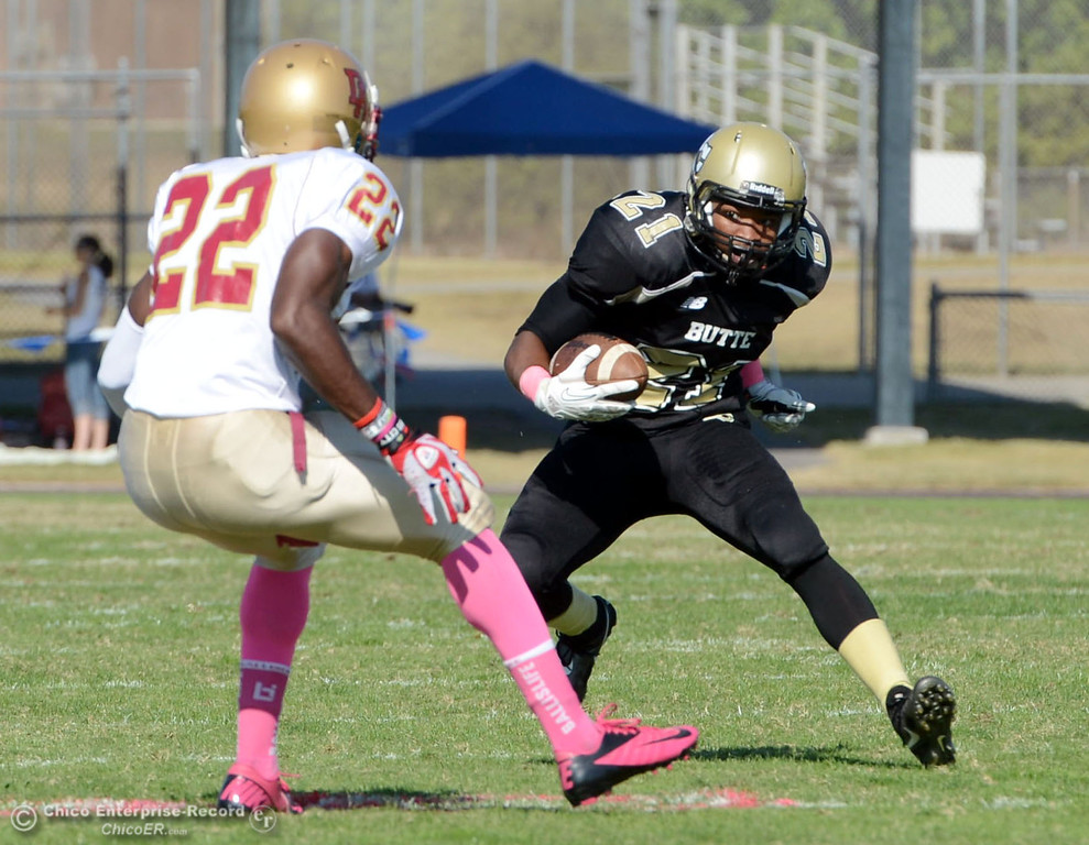 Description of . Butte College's #21 Marvel Harris (right) rushes against De Anza College's #22 Nathan Nelson (left) in the second quarter of their football game at Butte's Cowan Stadium Saturday, October 26, 2013 in Oroville, Calif.  (Jason Halley/Chico Enterprise-Record)